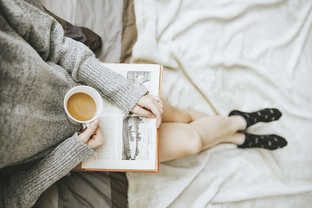 Girl with coffee reading a book