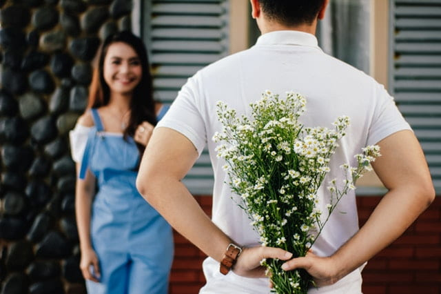 Guy with flowers behind his back
