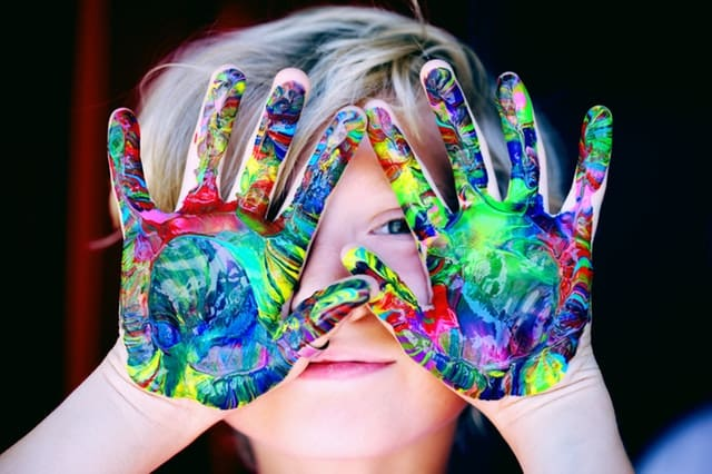 Child with hand full of paint
